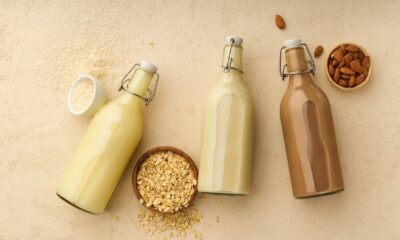 Dairy alternative. Rice, oat and chocolate almond milk in glass bottles on beige background. Healthy protein vegan drink. View from above